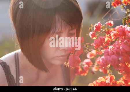 Beautiful young Asian woman with short black hair smelling a orange bougainvillea flower on a summer day with sun - Stock Photo