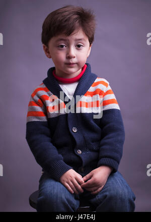 Portrait of sad serious multi-racial Asian Caucasian little boy with brown hair in a blue knitted sweater with orange - Stock Photo