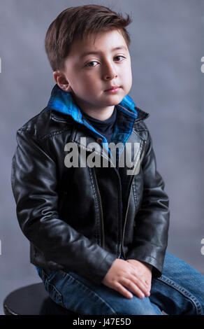 Punk rock and roll little boy with rockabilly greaser haircut wearing a black leather motorcycle jacket and blue - Stock Photo