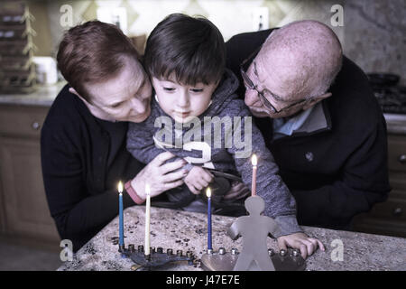 Jewish Family of grandparents and grandson lighting Hanukkah Candles in a menorah for the holdiays - Stock Photo