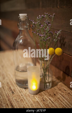Yellow and Purple dried flowers and lavender flowers in Ball glass jar between vintage water bottle and small candle - Stock Photo