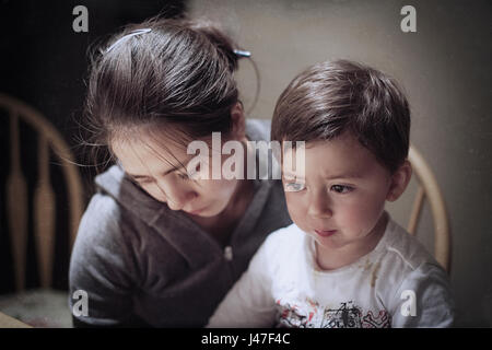 Dramatic portrait of a young Asian woman and her young son mourning the death of a father - Stock Photo