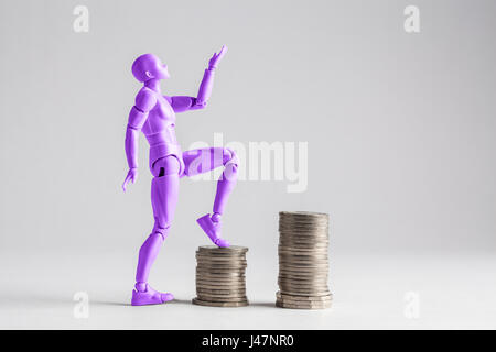 Empowered women stepping up the income ladder concept. Purple female figurine clilmbing up on piles of coins. Isolated - Stock Photo