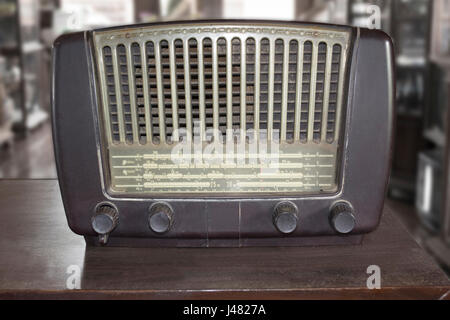 Old retro radio on wooden table in antique store. - Stock Photo
