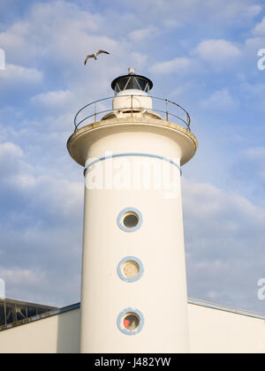 Seagull flying on a old lighthouse tower. Blue sky with some white clouds in background - Stock Photo