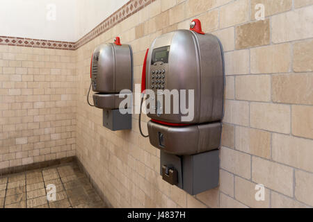 Room of coin operated pay telephones in Sienna, Italy - Stock Photo