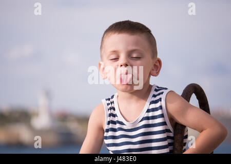 Funny boy in sailor vest showing tongue - Stock Photo