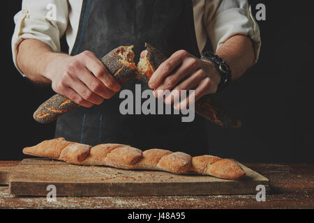 Hands breaking and separating fresh organic baguette - Stock Photo