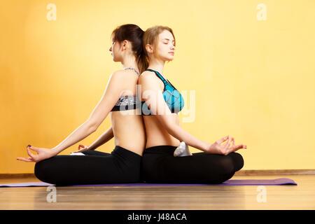 Two girls in lotus pose - Stock Photo