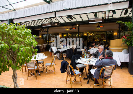 Dining on the terrace at the Cafe de Paris, next door to the Casino Monte Carlo, Monte Carlo, Monaco. - Stock Photo