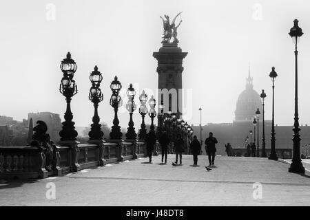 People walks on the historical Bridge Alexandre III ( Pont Alexandre III ) in Paris. Black and White image. - Stock Photo