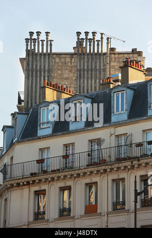 Chimneys on top of the roof of historical buildings in Paris - Stock Photo