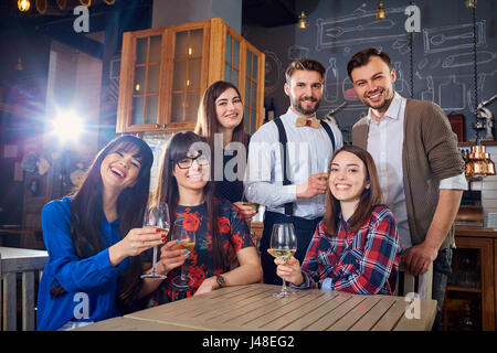 Group of friends at a meeting with glasses laugh and smile - Stock Photo