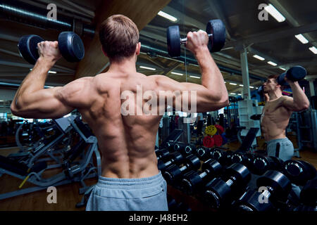 Rear view of a sporty man with dumbbells in his arms in the gym - Stock Photo