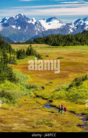 A small group of women hiking along a stream in Turnagain Pass, with patches of snow on the Chugach Mountains in - Stock Photo