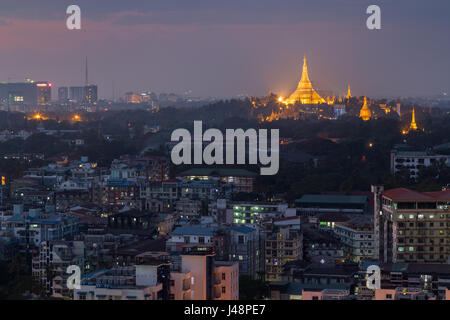 Apartment buildings and lit Shwedagon Pagoda in Yangon, Myanmar, viewed from above in the evening. - Stock Photo