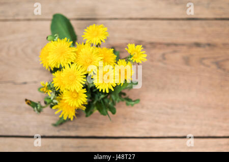 Bouquet of yellow dandelions with leaves on an old wooden table, top view - Stock Photo