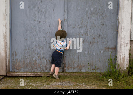 Young Boy Trying To Open Barn Door; Farnham, Quebec, Canada - Stock Photo