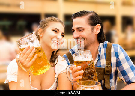 Young couple flirting in Oktoberfest beer tent while drinking beer - Stock Photo
