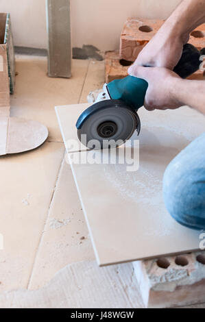 A Construction Worker Cutting A Tile Using An Angle Grinder Stock