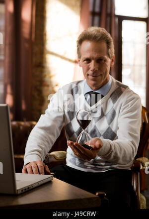 Psychiatrist man smiling for camera and holding hourglass in hand while waiting for patients in his office. Portrait - Stock Photo