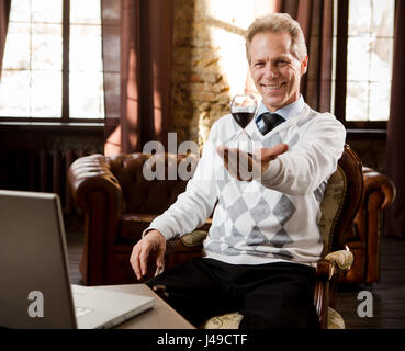 Portrait of handsome psychiatrist man smiling and looking at camera. Psychiatrist man holding and representing hourglass - Stock Photo