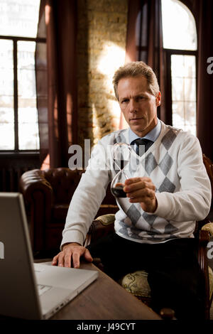 Portrait of psychiatrist man holding hourglass and looking at camera while sitting in front of laptop computer in - Stock Photo