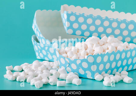 pile of small colored puffy marshmallows isolated on aquamarine background close up - Stock Photo