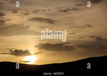 Sunrise on a bit cloudy sky over mountains silhouette - Stock Photo