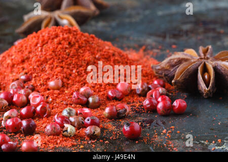 Closeup red pepper with ground paprika on dark - Stock Photo