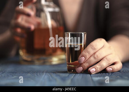 Drunk woman holding an alcoholic drink, Focused on the drink - Stock Photo