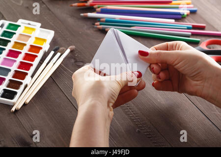 adult woman do origami boat from paper sheet - Stock Photo