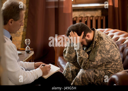 Military man communicating with psychologist. Psychologist providing moral assistance to soldier who has been in - Stock Photo