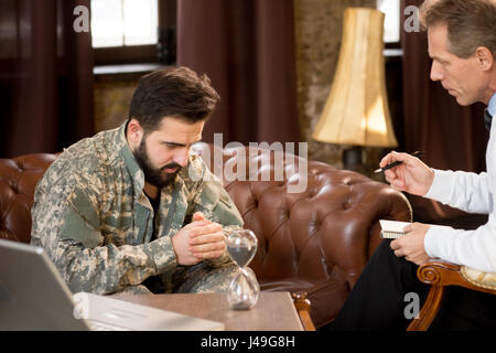 Military man listening to psychologist at psychologist's office. Military psychologist trying to solve his problems. - Stock Photo