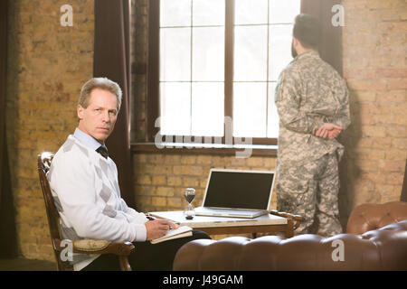 Portrait of military psychologist communicating with military man and providing moral assistance to soldier who - Stock Photo