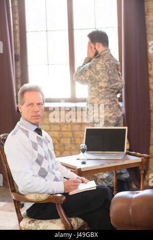 Military man staying near window at psychologist's office. Portrait of military psychologist communicating with - Stock Photo