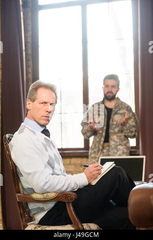 Military psychology concept. Military man staying near window at psychologist's office. Portrait of military psychologist - Stock Photo