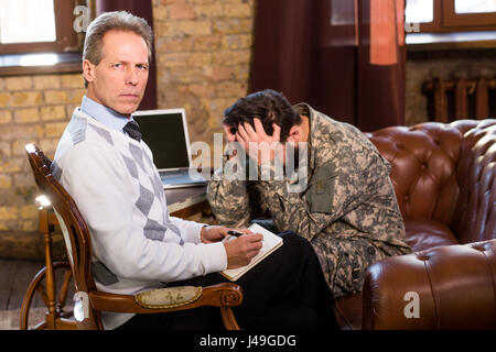 Communication of military psychologist and military man concerning existing problems in his life. Military man touching - Stock Photo