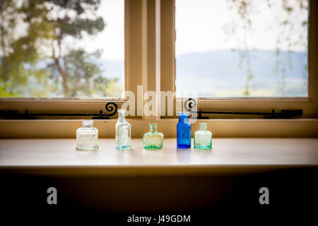 Refined country living - Five stylish little glass bottles sitting on a window sill - Stock Photo