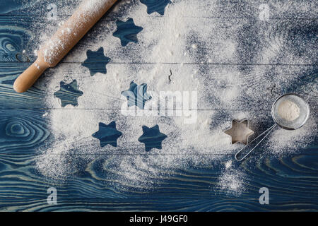 Christmas stars on flour background with copy space. White flour looks like snow. Top view - Stock Photo