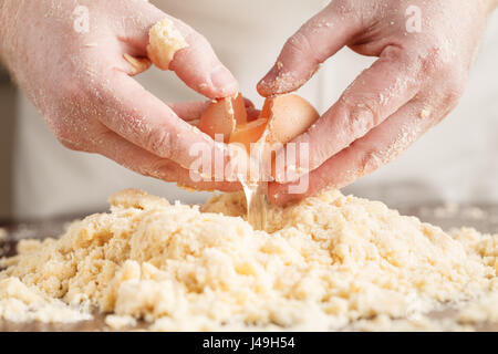 handful of flour with egg on a rustic kitchen. Against the background of men's hands knead the dough. Ingredients - Stock Photo