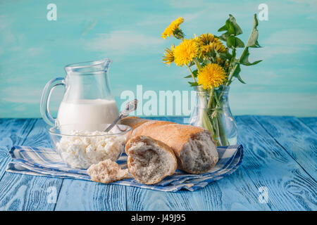 organic healthy food, cottage cheese and bread. Dandelion flowers on table - Stock Photo