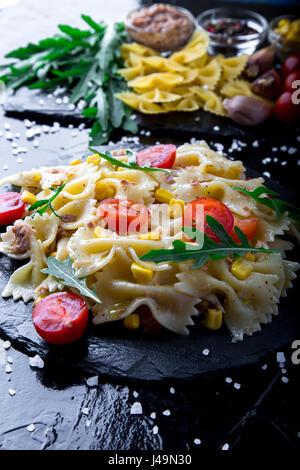 Pasta salad in slate plate with tomatoes cherry, tuna, corn and arugula.  ingredients. Italian food - Stock Photo