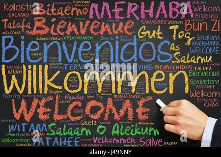 Hand writes welcome in many international languages with colorful chalk on blackboard - Stock Photo