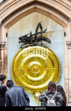 Tourists examine the chronophage (time-eater) and large clock designed by John Taylor outside Corpus Christi college - Stock Photo