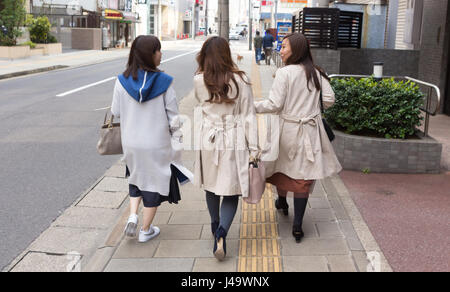 Nagasaki, Japan - March 26th, 2017: Three japanese girls walking on the sidewalk, two of them wearing trench coat. - Stock Photo