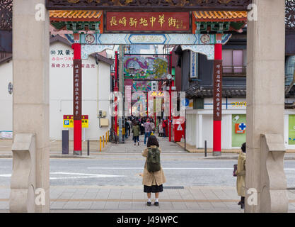 Nagasaki, Japan - March 26th, 2017: A japanese girl wearing a trench coat and backpack is taking a photo of the - Stock Photo