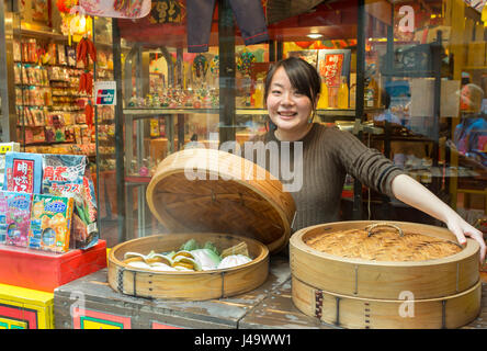 Nagasaki, Japan - March 26th, 2017: A chinese vendor selling steamed pork buns on the street at the pedestrian street - Stock Photo