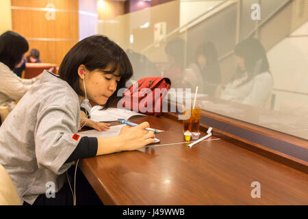 Nagasaki, Japan - March 26th, 2017: Japanese girl writing and listening music sitting inside a coffee shop in Nagasaki. - Stock Photo