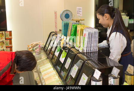 Nagasaki, Japan - March 26th, 2017: Japanese girl working inside a Green Tea Shop while a customer is looking down - Stock Photo